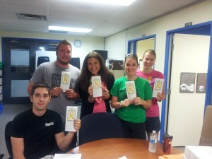 Student leaders hold up a suicide prevention brochure as they prepare the residence welcome packages